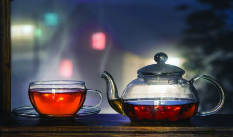 Tea cup with tea pot on the windowsill. Tea on a background of a night landscape. Tea time.